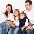 Cheeful young family watching TV at home - Stock Photo