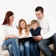 Hapy young family watching photo album — Stock Photo #20229173