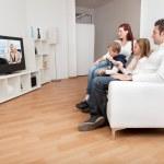 giovane famiglia guardando la tv a casa — Foto Stock