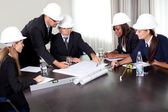 Mature male architect explaning his colleagues — Stock Photo