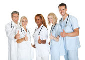 Group of doctors giving thumbs up sign over white — Stock Photo