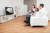 Young family watching TV at home — Stock Photo