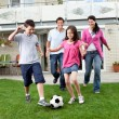 Happy family playing football in their backyard — Stock Photo