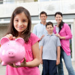 Girl saving money with family at the back — Stockfoto