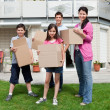 Family carrying boxes into new home — Stock Photo