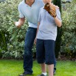 Foto Stock: Cute little boy playing baseball with his father
