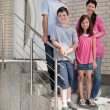 Happy young family standing at doorstep — Stock Photo