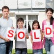 Family holding a sold sign outside their home — Stock Photo