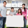 Young family holding a black white board — Stock Photo