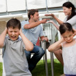 Children suffers while parents fight in background — Stockfoto