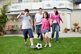 Happy family playing football in their backyard — Stockfoto