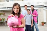 Girl saving money with family at the back — Foto de Stock