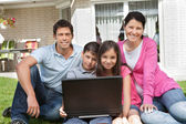 Happy family sitting together with laptop — Stock Photo