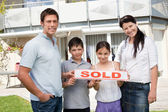 Smiling young family buying new house — Stock Photo