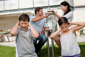 Children suffers while parents fight in background — Stock Photo