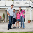 Caucasian family standing in front of house — Stock Photo