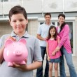 Small boy saving money with family at the back — Stock Photo