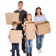 Happy young family carrying boxes — Stock Photo