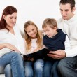 Hapy young family watching photo album — Stock Photo