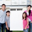 Happy family outside with a blank sign board - Stock Photo