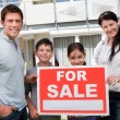 Young family selling their home with sale sign — Stock Photo