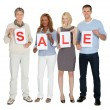 Businesspeople holding white paper with word sale — Stock Photo
