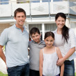 Caucasian family outside their new house — Foto Stock