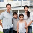 Caucasian family outside their new house — ストック写真