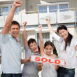 Happy family celebrating buying their new house - Stock Photo