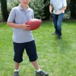 Foto Stock: Little boy and father playing american football
