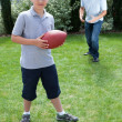 Stock Photo: Little boy and father playing american football