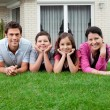 Portrait of family of four lying in backyard — Stock Photo #21241339