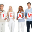 Happy group of holding team sign board — Stock Photo