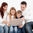 Happy family using laptop at home — Stock Photo #21241441