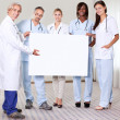 Happy group of doctors holding a blank placard — Stock Photo #21241739