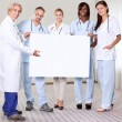 Happy group of doctors holding a blank placard - Stock Photo