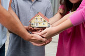 Human hands holding a model of house — Stock Photo