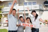 счастливая семья празднует, покупая их новый дом — Стоковое фото