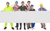 Groupe de travailleurs présentant une bannière vide — Photo