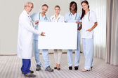 Happy group of doctors holding a blank placard — Stock Photo