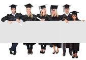 Grupo de estudiantes graduados que presenta vacío banner — Foto de Stock