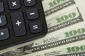 Närbild på miniräknare och dollar — Stockfoto