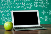 Laptop and apple on the desk — Stock Photo