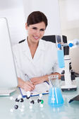 Female Scientist Writing On Paper — Stock Photo