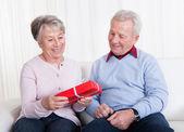 Senior man geschenk geven senior vrouw — Stockfoto