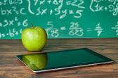 Cyfrowe tabletki i jabłko na biurku — Zdjęcie stockowe