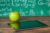 Dijital tablet ve masanın üstünde elma — Stok fotoğraf
