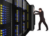 Businessman pushing server rack in place — Stock Photo
