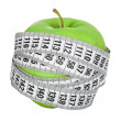 Apple wrapped in measuring tape - Stock Photo