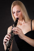 Beautiful young woman playing clarinet — Zdjęcie stockowe